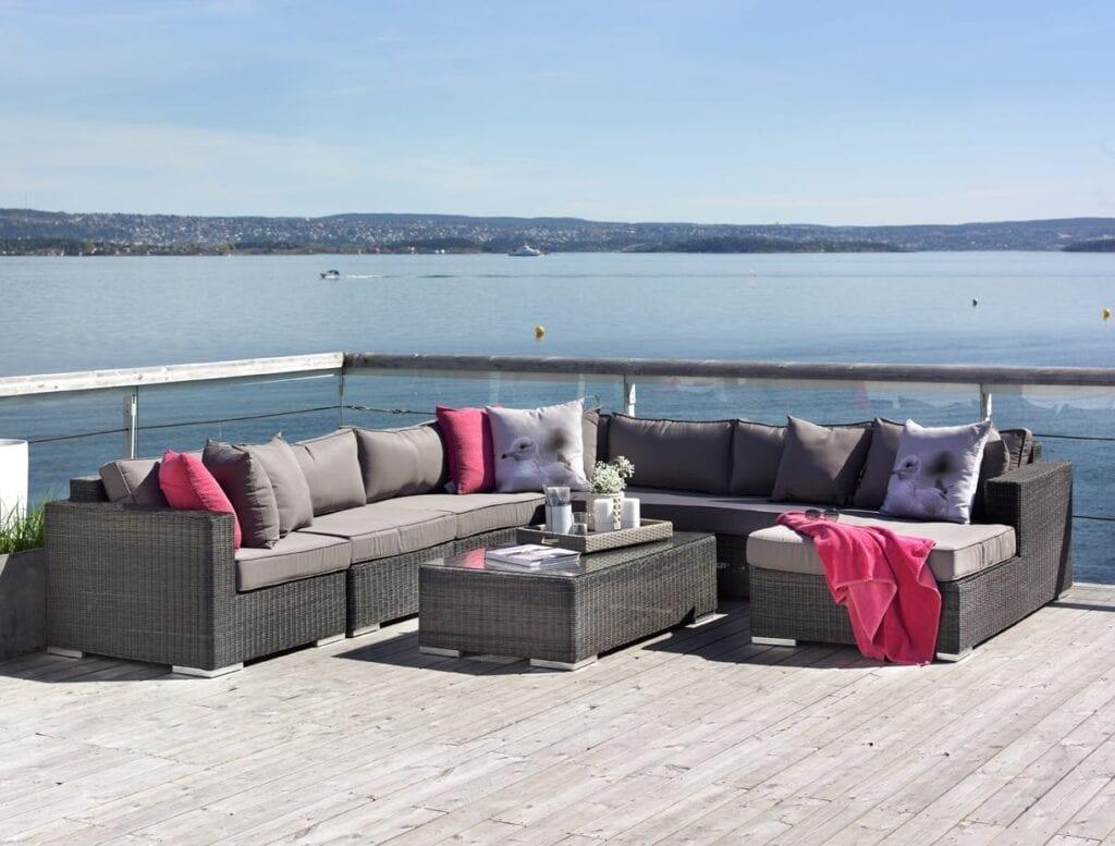 Hagemøbler og utemøbler fra Fine Design. En stor hagesofa i rotting står på en terrasse sammen med et rottingbord som har en glassplate. Man ser sjøen i bakgrunnen.