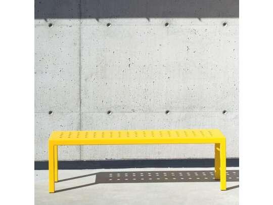 Gul benk foran betongvegg i sollys