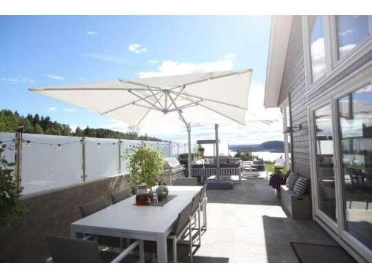 Stort, hvitt hagebord i aluminium på uteplass under parasoll