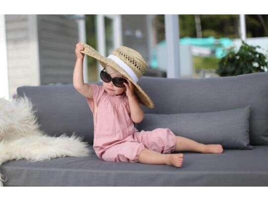 Barn med solbriller og strandhatt sitter i sofa og koser seg