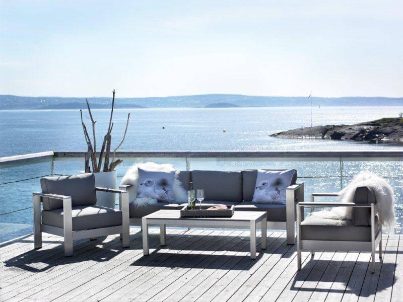Hagemøbler og utemøbler fra Fine Design. To stoler og en treseter står på en terrasse sammen med et likt bord. Man ser sjøen i bakgrunnen.