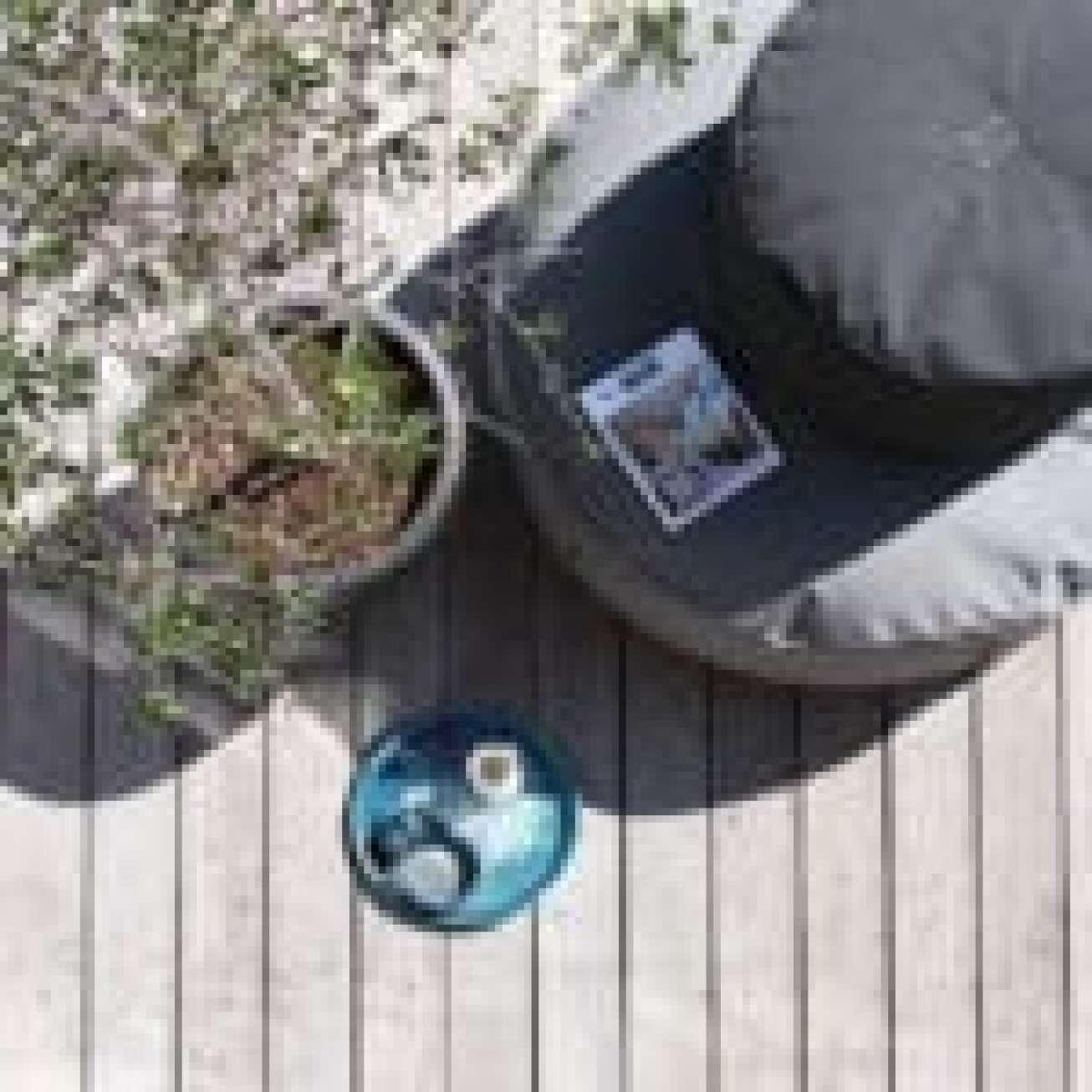 Trimm Copenhagen Tiny moon medium puff i sort og Full moon large puff i grå i sollys på veranda