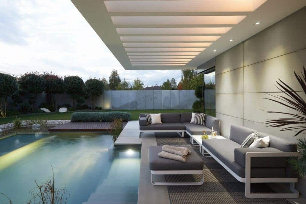 Gardenart lounge møbler hvit aluminium og grå puter med bord imellom og fotpall ved bassengen i uteplassen