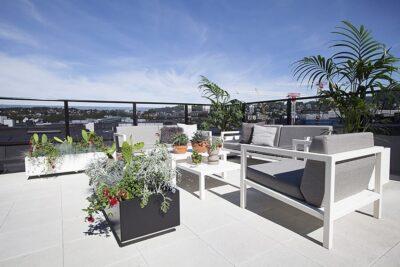 En fin hvit sittegruppe på en terrasse sammen med en plantekasse fra BEDD