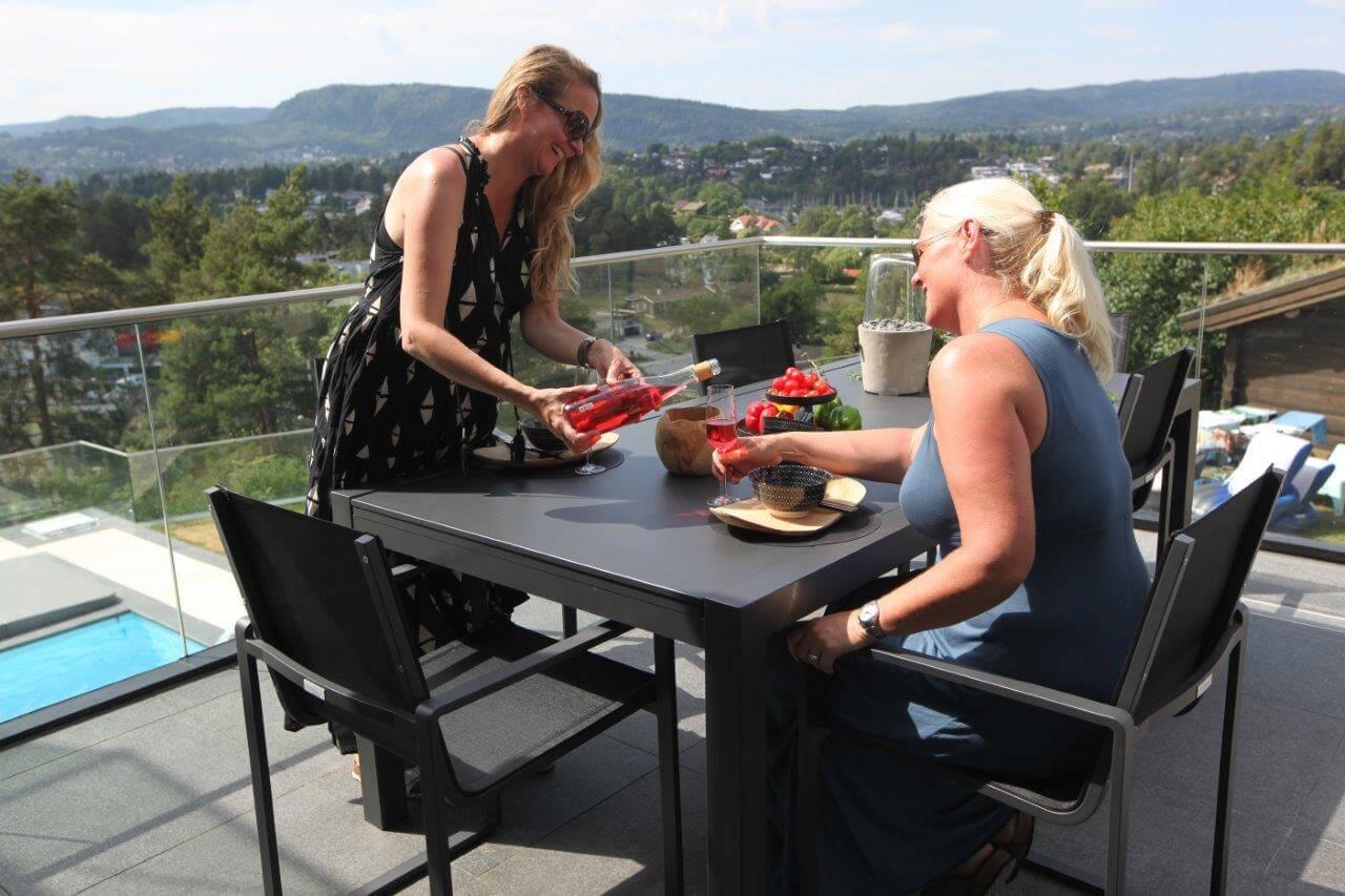 To damer sitter på veranda, ved firkantet spisebord og drikker vin