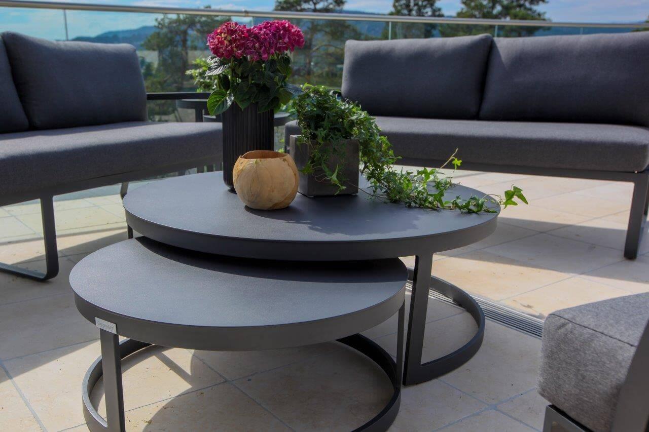 Gardenart runde bord i sort aluminium med blomster og grå utesofaer i bakgrunn