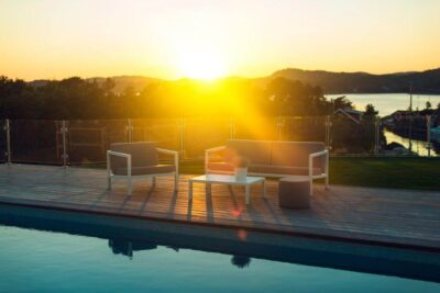 Sundays Design sittegruppe på platting ved siden av basseng. Solnedgang og sommer.