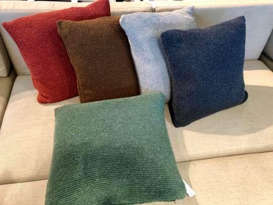 Puter i ribbestrikk i 100 % ull i mange farger på en komfortabel sofa i beige