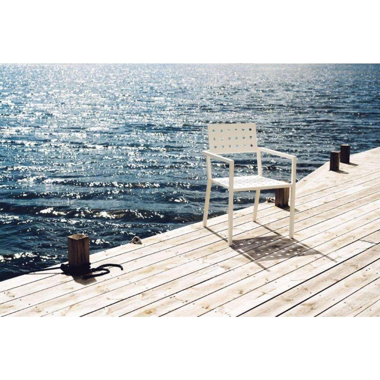 Sundays Frame spisestol i hvit aluminium i sollys, på platting ved havet