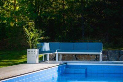 En fin hagesofa i alumiunium fra Sundays Design står ved bassenkanten