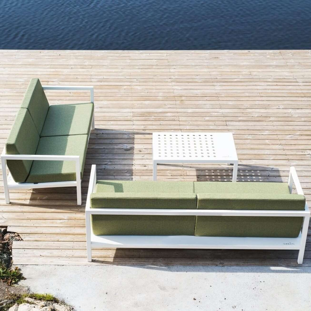 To toseter sofaer i hvit aluminiumsramme og grønne puter, med hvitt bord ute i solen ved vann