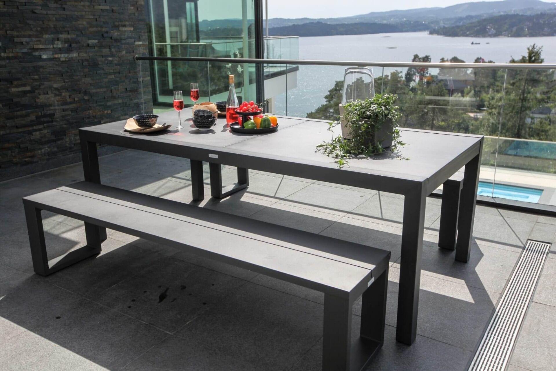 Spisebenker og oppdekket spisebord på balkongen med utsikt mot vann