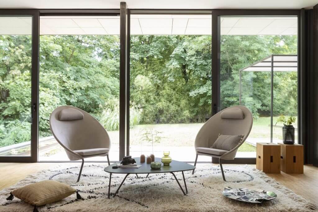 Hagemøbler og utemøbler fra Fine Design. To stoler står i en vinterhage. Store vinduer, grønne trær utenfor.