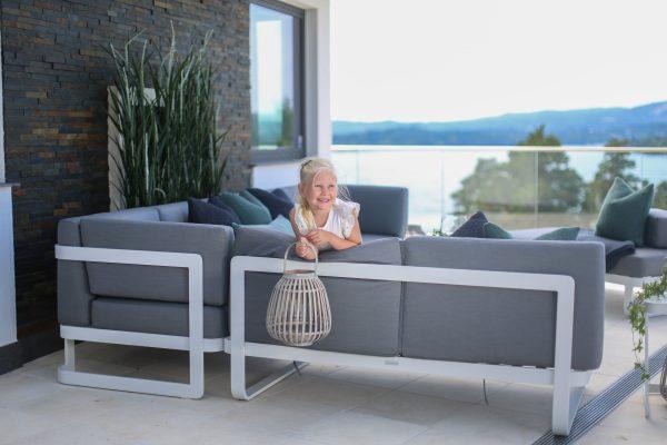 Hagemøbler og utemøbler fra Fine Design. Liten jente holder en lykt. Hun sitter i en stor, grå hagesofa.