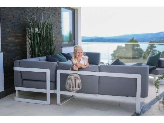 Liten jente holder en lykt og sitter i en stor, grå hagesofa på veranda med flott utsikt
