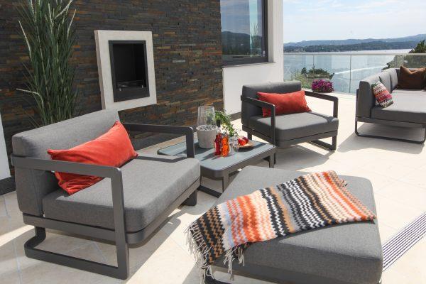 Hagemøbler og utemøbler fra Fine Design. To behagelige hagestoler står på en terrasse sammen med en puff og et lite firkantet bord.