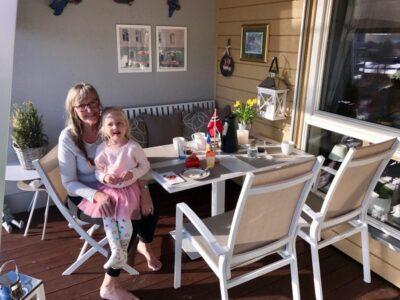 Fine Design spisegruppe på en liten terrasse. I en stol sitter en eldre dame med en liten jente på fanget