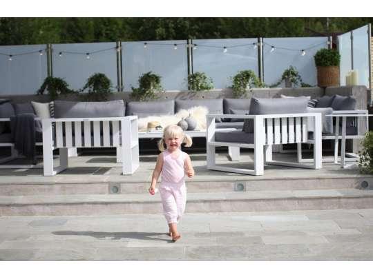 Liten jente foran hvit sofagruppe i aluminium med grå puter