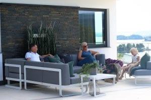 Hagemøbler og utemøbler fra Fine Design. Flere mennesker sitter å koser seg i en stor og fin loungesofa. Grå sofa med et hvitt bord.