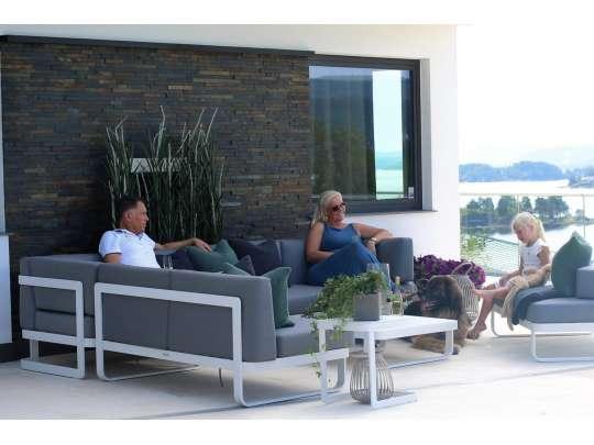 En familie sitter og koser seg i en stor og fin loungesofa med hagebord i hvit aluminium med grå tekstil