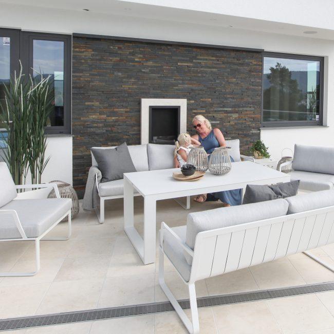 Hagemøbler og utemøbler fra Fine Design. Daglig leder i Fine Design, Marianne Aanerød sitter i en hagesofa sammen med datteren sin. Hvite hagemøbler med grå puter.