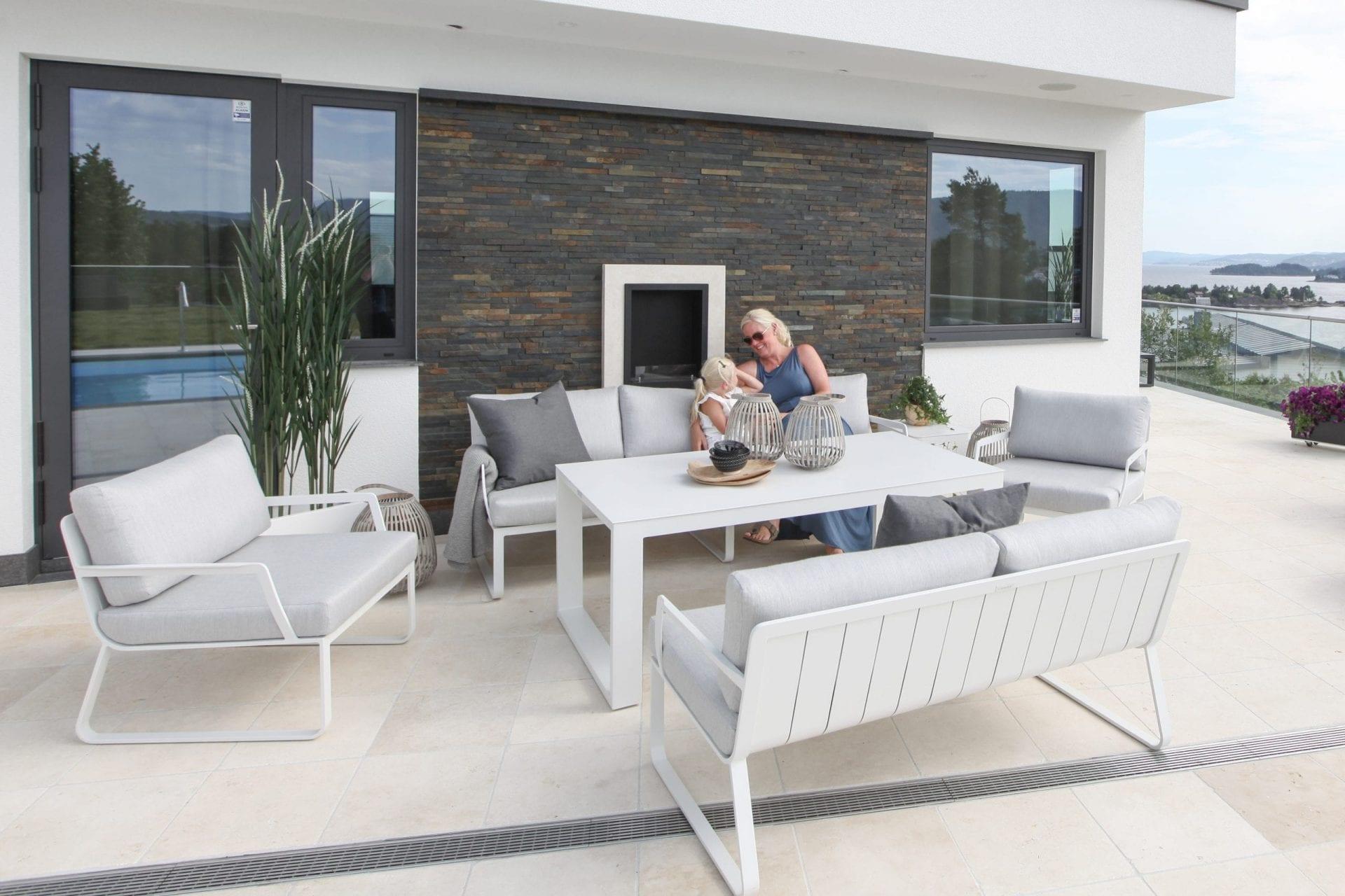 Hagemøbler og utemøbler fra Fine Design. Marianne sitter i en hagesofa sammen med datteren sin.