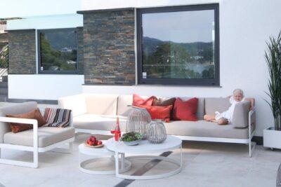 Hagemøbler og utemøbler fra Fine Design. Stor, lys hagesofa med lik stol. Liten jente sitter i sofaen.