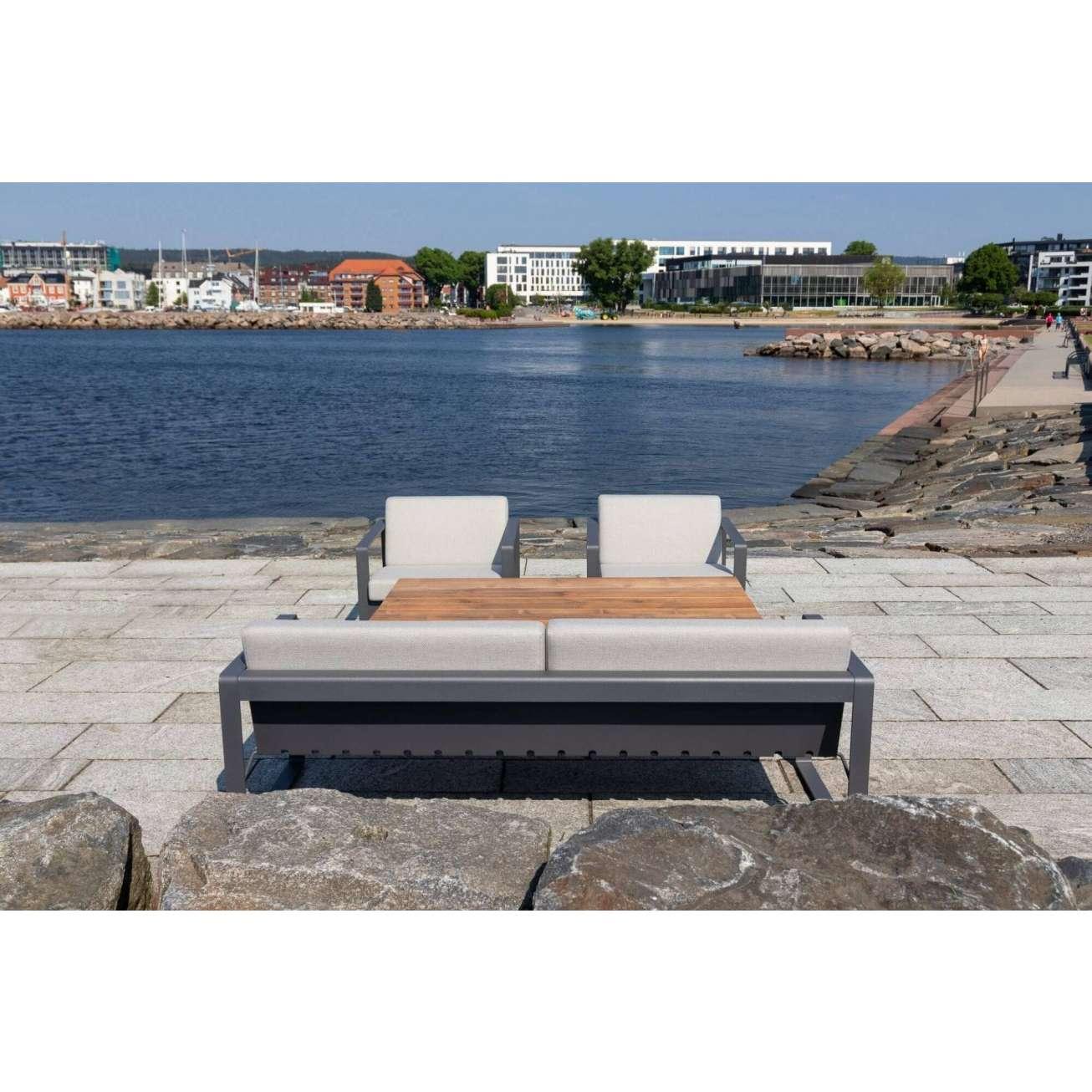Sundays Core sofagruppe i mørkgrå aluminium med puter i lys grå farge på uteplass ved havet