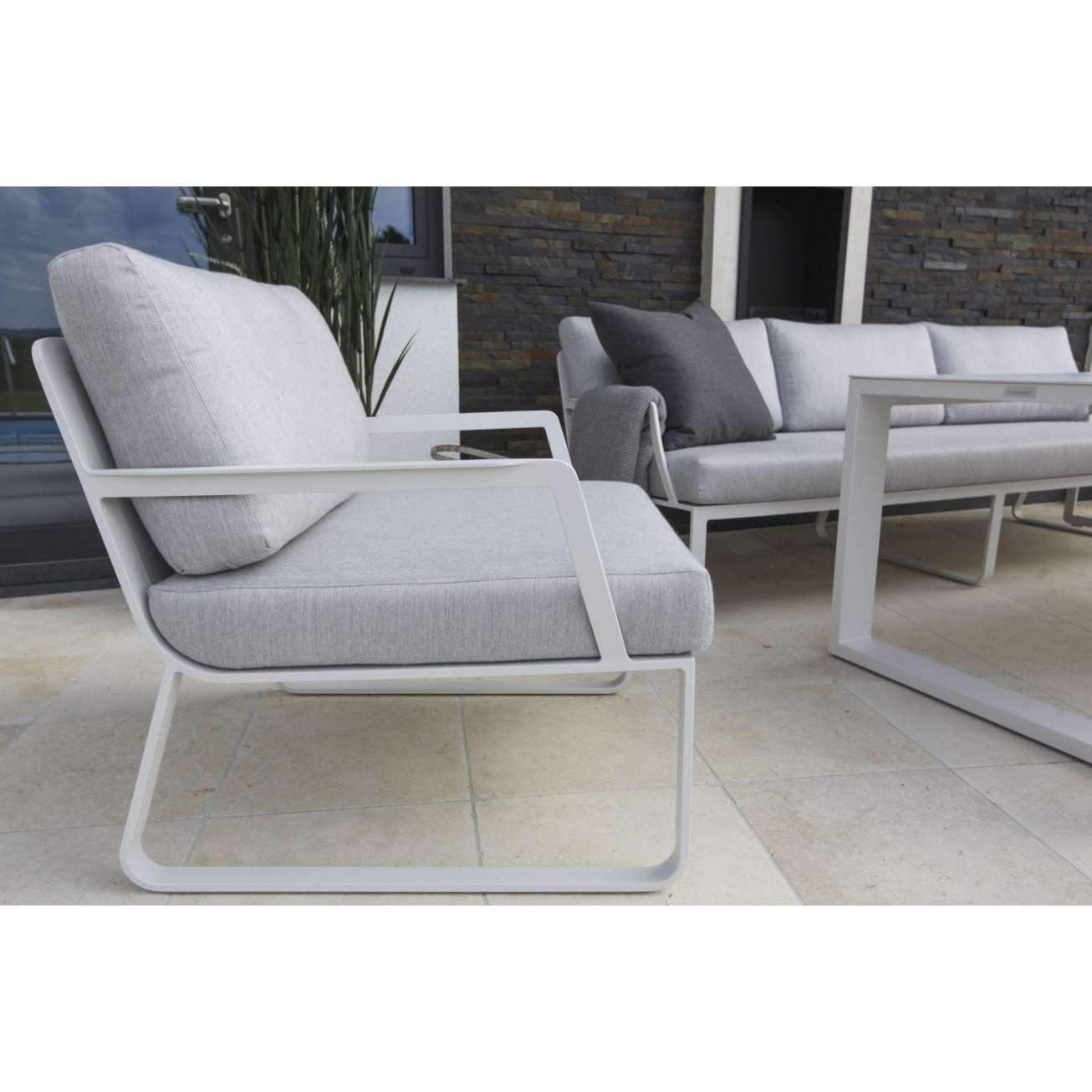 Nærbilde av hagestol i hvit aluminium med grå puter og en 3-seter sofa i bakgrunn