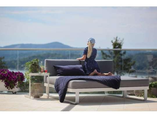 En liten jente sitter på veranda og koser seg i sollys på en sofa - toseter i hvit aluminium med grå puter