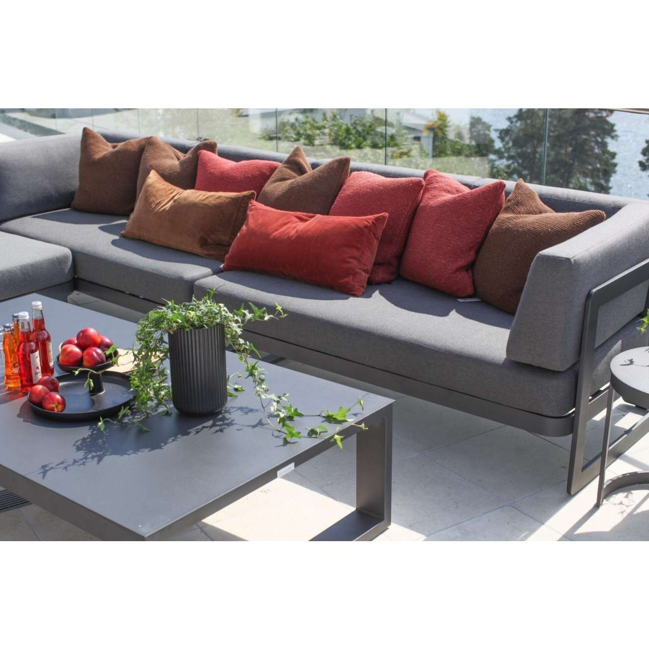 Hjørnesofa i sort aluminium med grå tekstil, pyntet med puter i flere farger og hagebord på terrasse i sollys