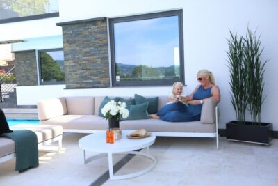 Hagemøbler og utemøbler fra Fine Design. Mor og datter sitter i en utesofa og koser seg.