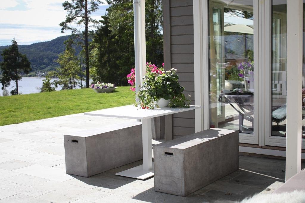 Hagemøbler og utemøbler fra Fine Design. Et fint hvitt aluminiumsbord står sammen med to massive betongkrakker på et uteområde.