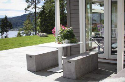 Et hvitt aluminiumsbord sammen med to massive betongbenker i sollys i en hage