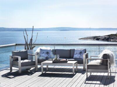 Sofagruppe på platting i sommersol ved sjøen