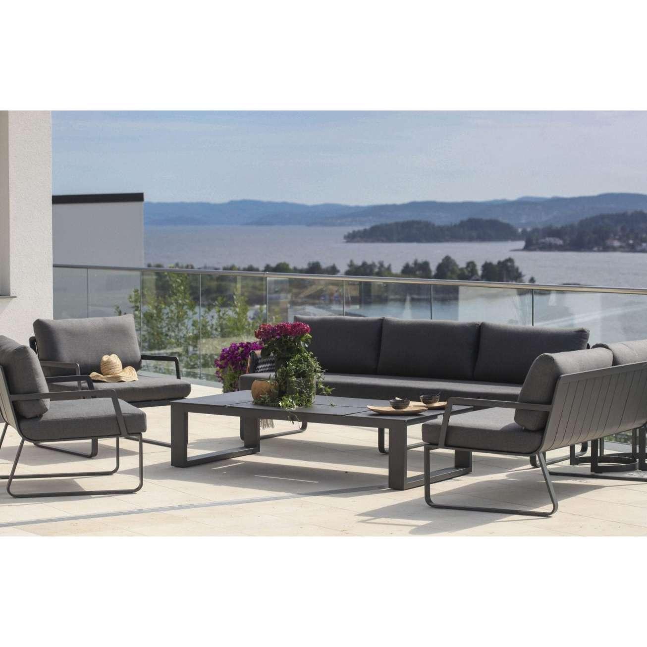 Sofagruppe - 3-seter og tre hagestoler i sort aluminium med grå puter sammen med et hagebord på veranda