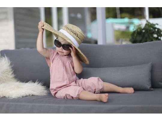 En liten jente sitter på veranda og koser seg i sollys på en grå sofa
