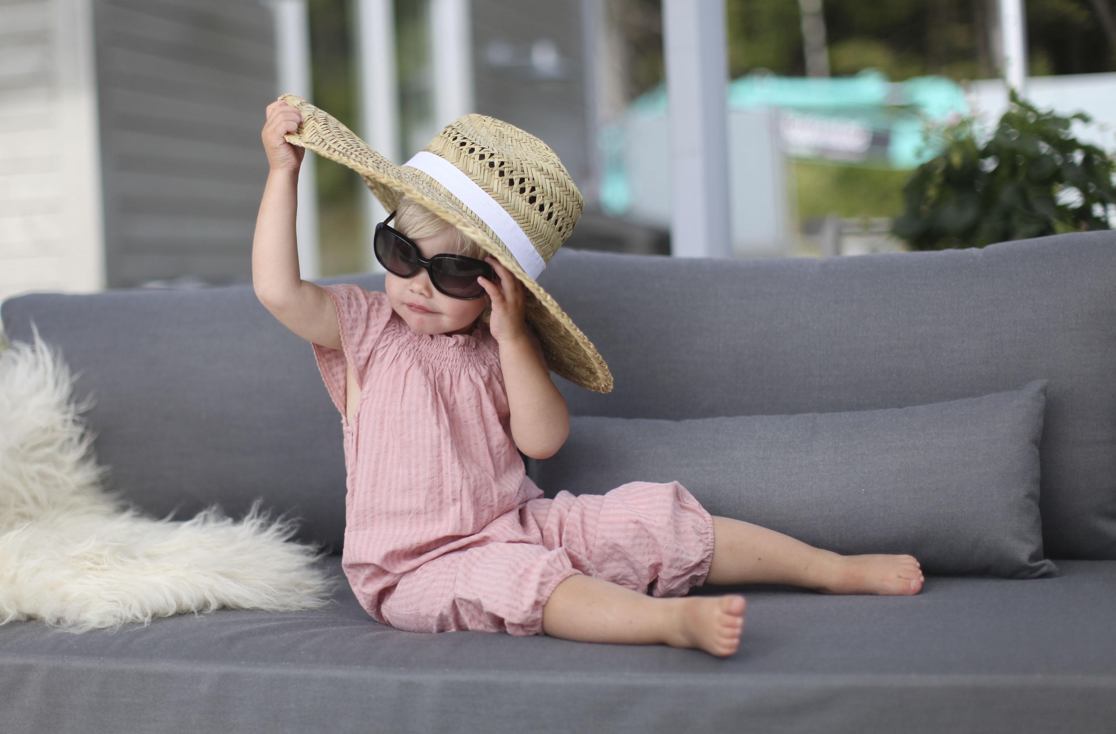 Hagemøbler og utemøbler fra Fine Design. En ung jente sitter i en hagesofa med en stor solhatt og solbriller.