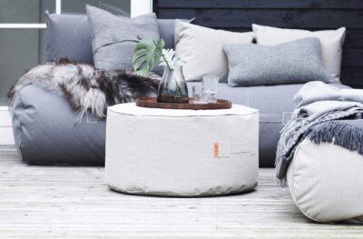 En fin puff fra TRIMM står på en terrasse med Rocket Daybed Sofa i grå og dekorative puter på uteplass
