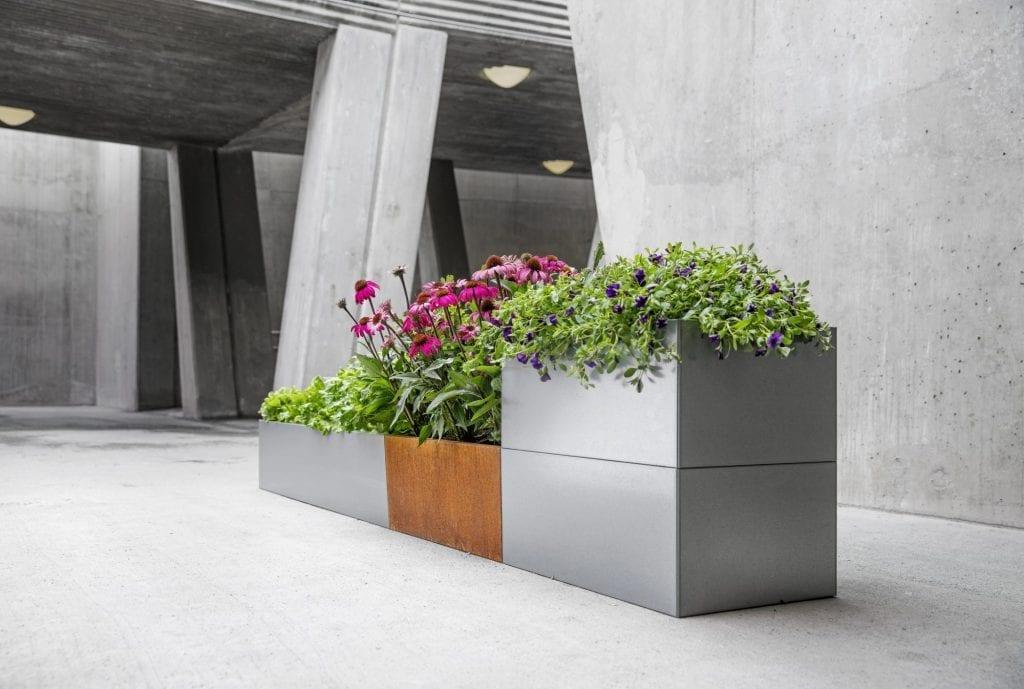 Hagemøbler og utemøbler fra Fine Design. Flere plantekasser fra BEDD satt sammen til et større bedd. Tre i rustfritt stål. en i ubehandlet, rustet, stål. Fine blomster.