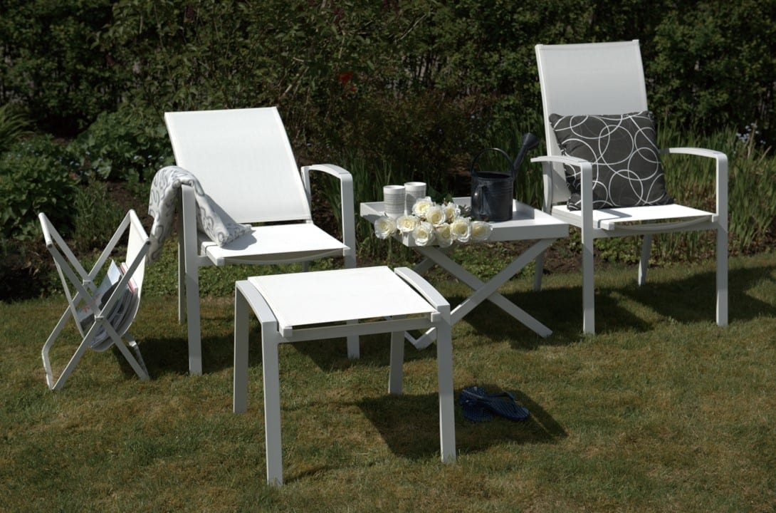 Hagemøbler og utemøbler fra Fine Design. To fine hagestoler står sammen med en liten puff og et lite bord i en hage.