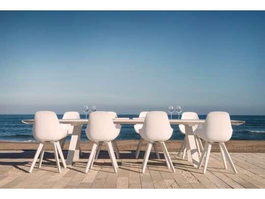 hvit spisebord med åtte spisestol ved havet