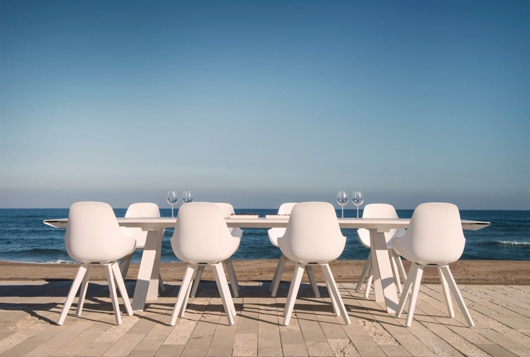 Hagemøbler og utemøbler fra Fine Design. Et hvitt spisebord med åtte hvite stoler, stående nede ved vannet.