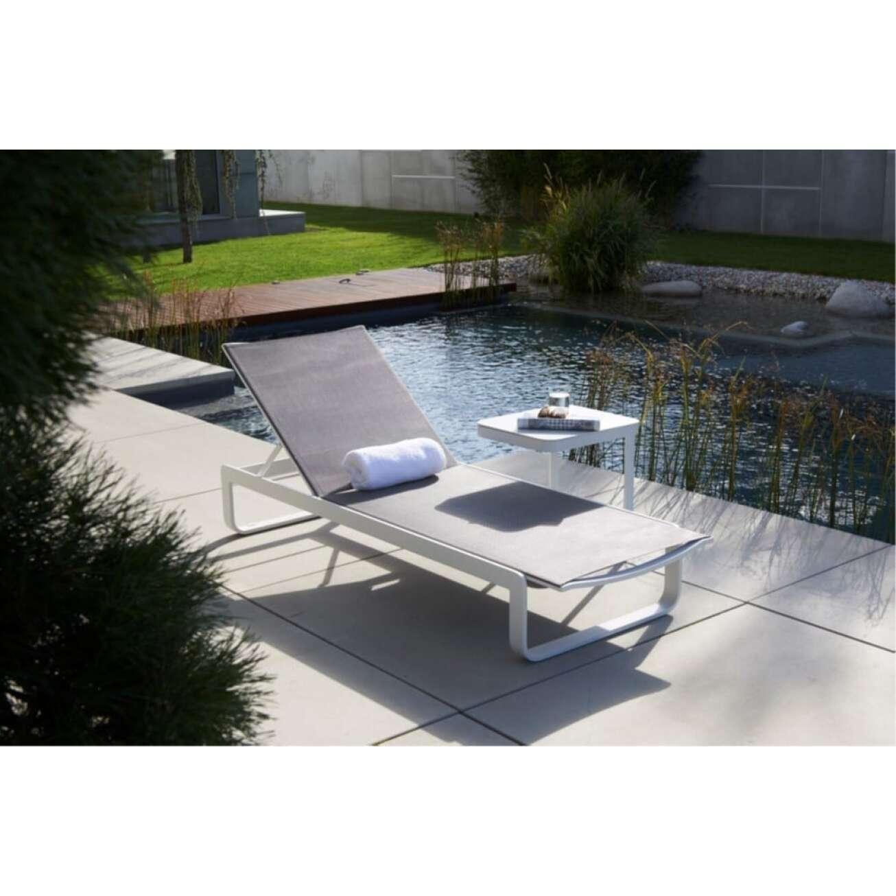 Solgseng med hvit ramme og grå tekstil med bord ved vann
