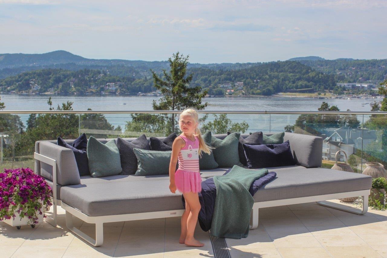 Hagemøbler og liten jente i rosa sommerkjole på terrasse med fantastisk utsikt Hagemøbler og utemøbler - Fine design