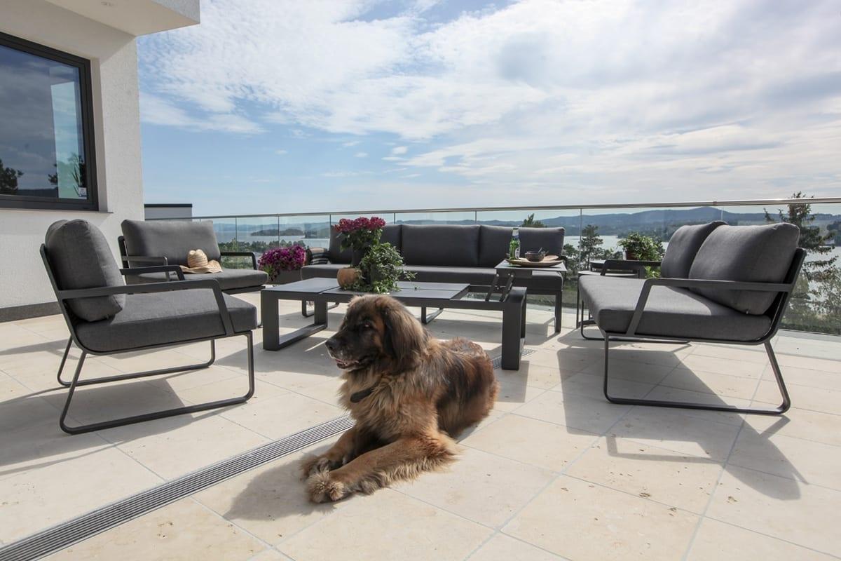 Stor, solfylt terrasse med hund, utsikt og hagemøbler fra Fine Design