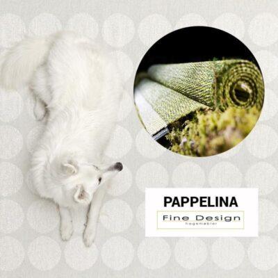 Hund poserer ved et Pappelina-teppe