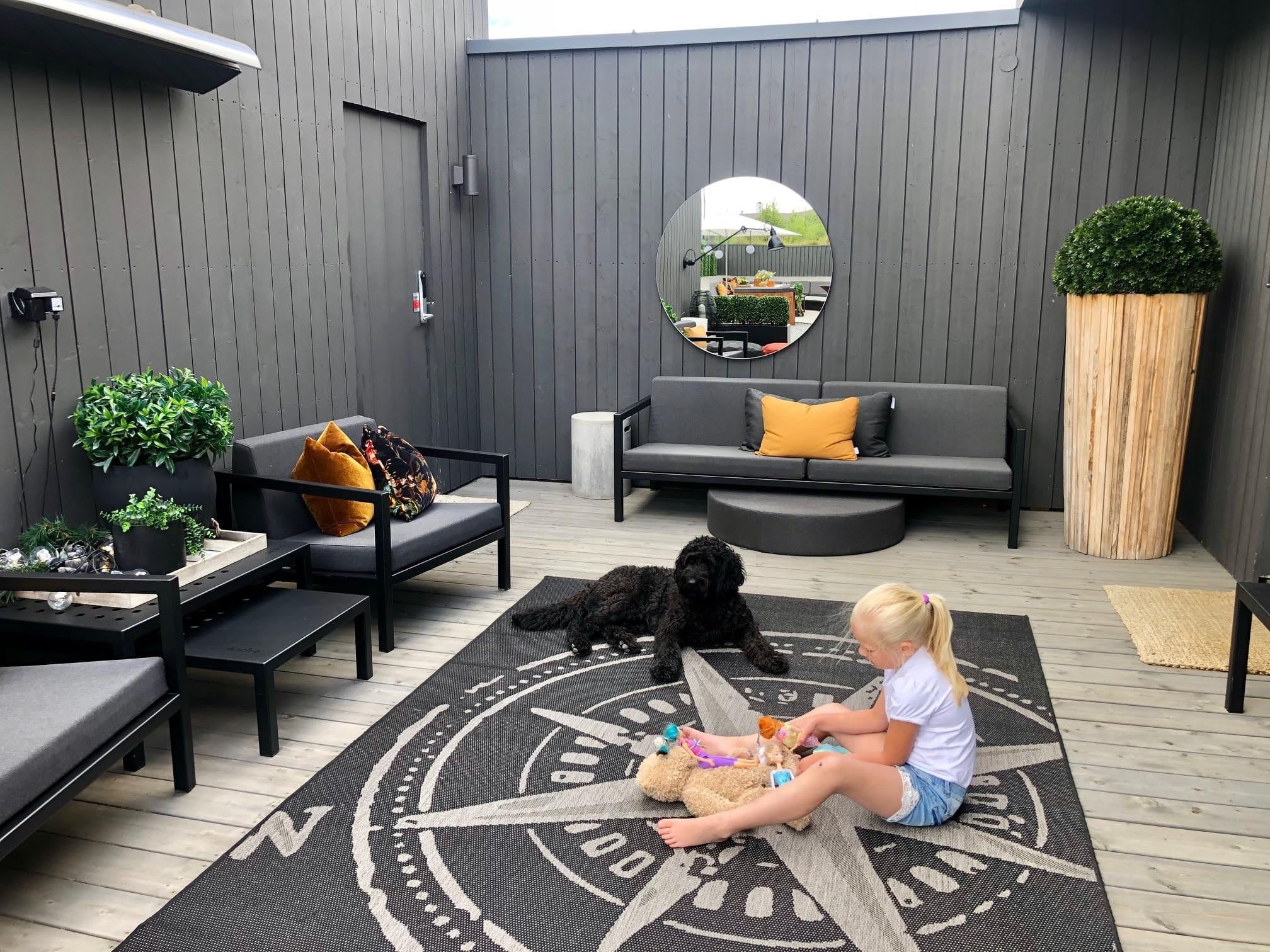 Uterom innredet med aluminiumshagemøbler og tepper der en liten jente leker mens hundenn ser på
