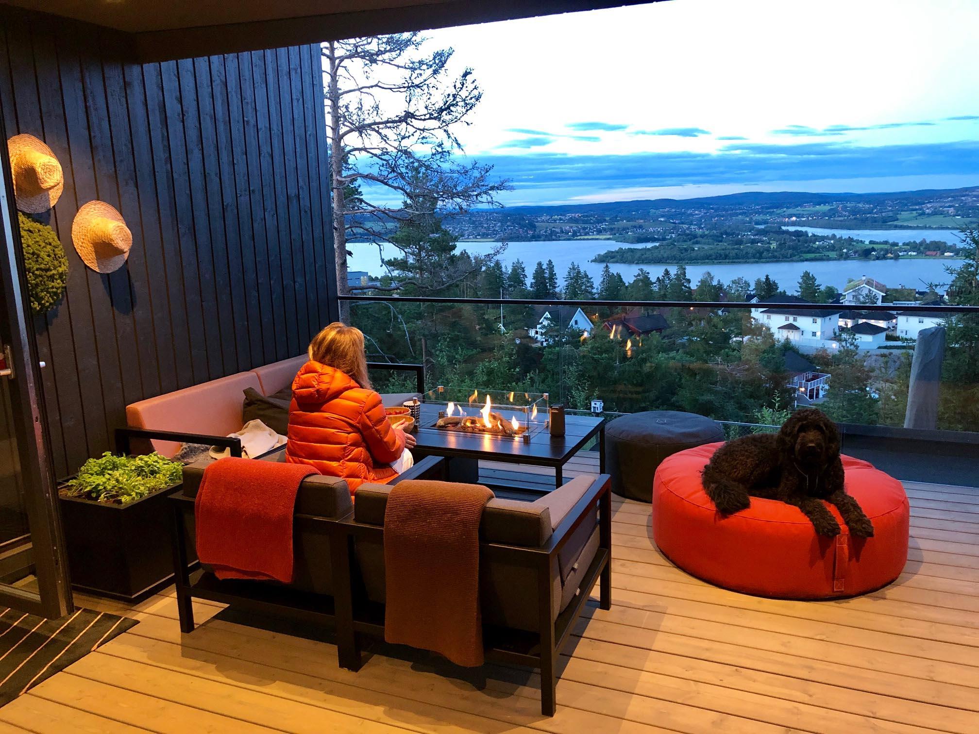 Kvinne i jakke sitter på terrassen i Fine Design hagemøbler - med hund som ligger på sittepuff