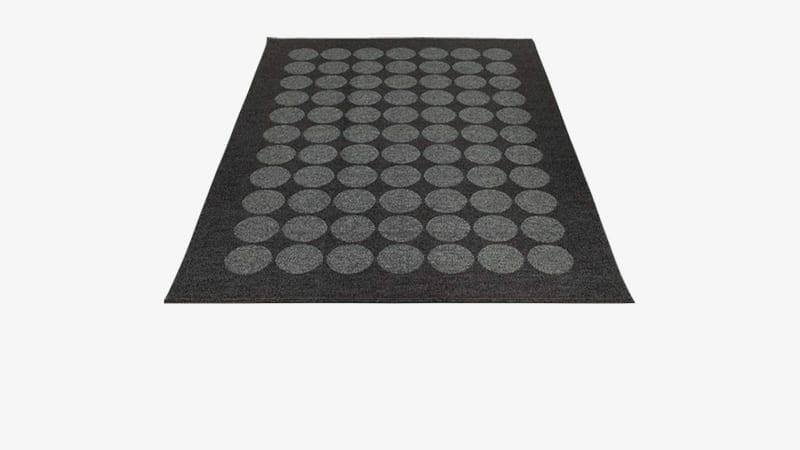 Pappelina teppe av mørkegrått stoff med lyse sirkler av samme dimensjon